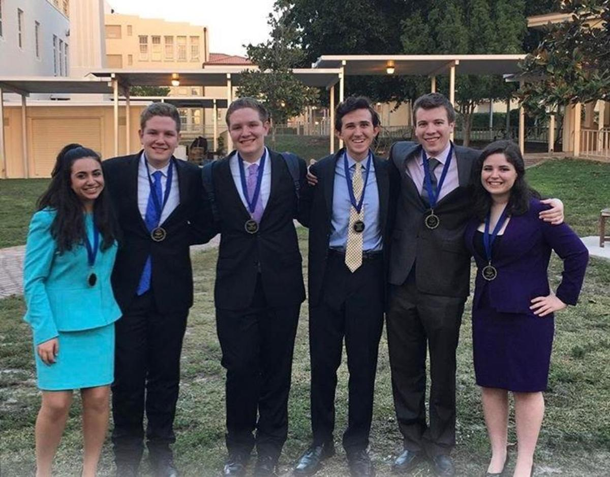Communications freshmen Mara Vaknin (L-R), Kevin Ahern, Kyle Ahern, junior Alex Gordon, senior Jake Perl, and junior Maya Levkovitz. Students who qualified for the national tournament at Kentucky in May 2017 pose with their medals after the Palm Beach Catholic Forensic League (PBCFL) Grand Finals award ceremony.