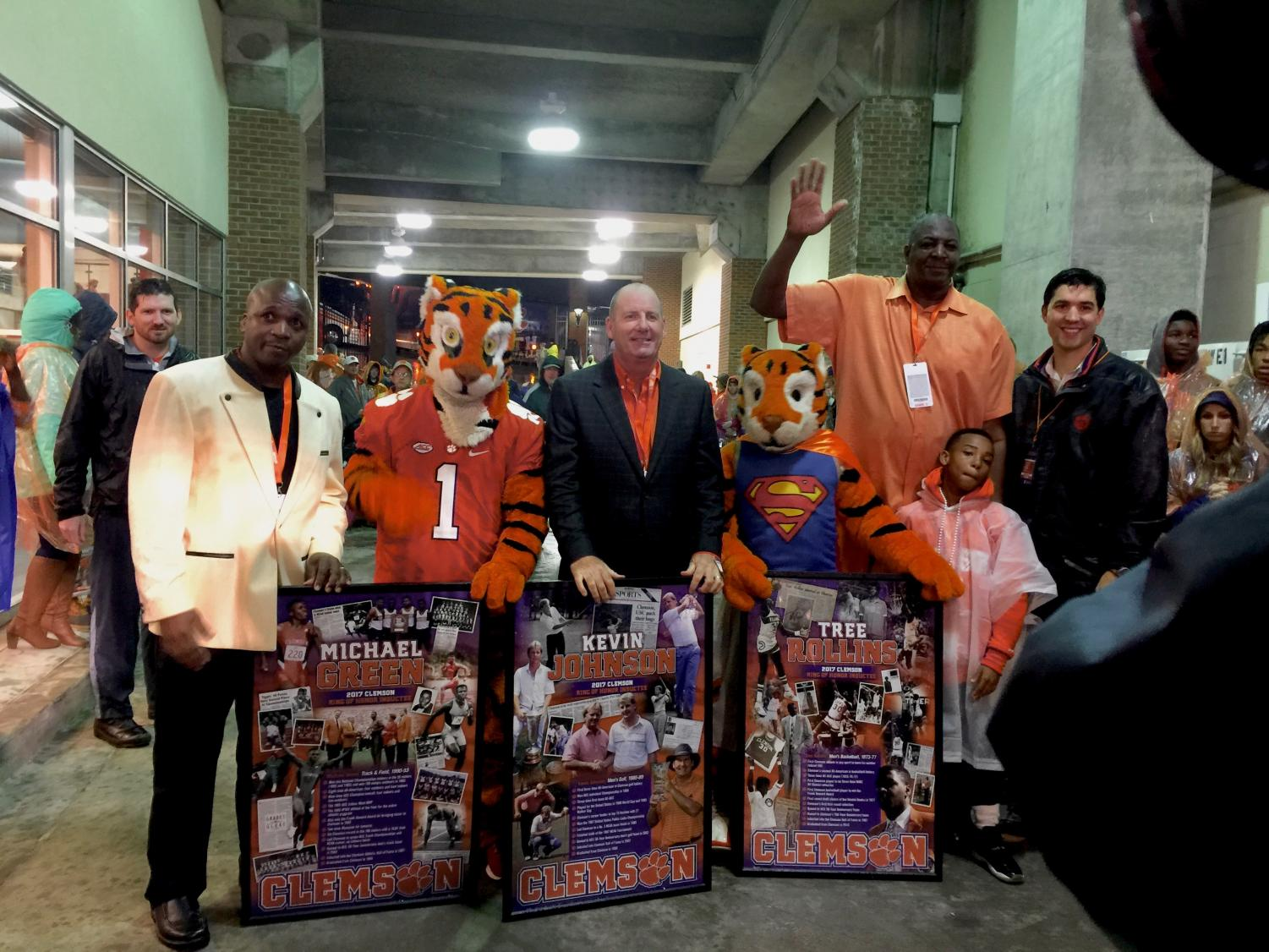 "Clemson University's Ring of Honor inductees, Michael Green, Kevin Johnson, and Tree Rollins stand with the Tiger mascots and face the cameras as they're shown with their awards. Moments before the three inductees ran onto the field to dot the ""i"" in the word, ""Tigers"" spelled out by the band, their images appeared on the jumbo screen before the football game against Georgia Institute of Technology on Oct. 28, 2017."