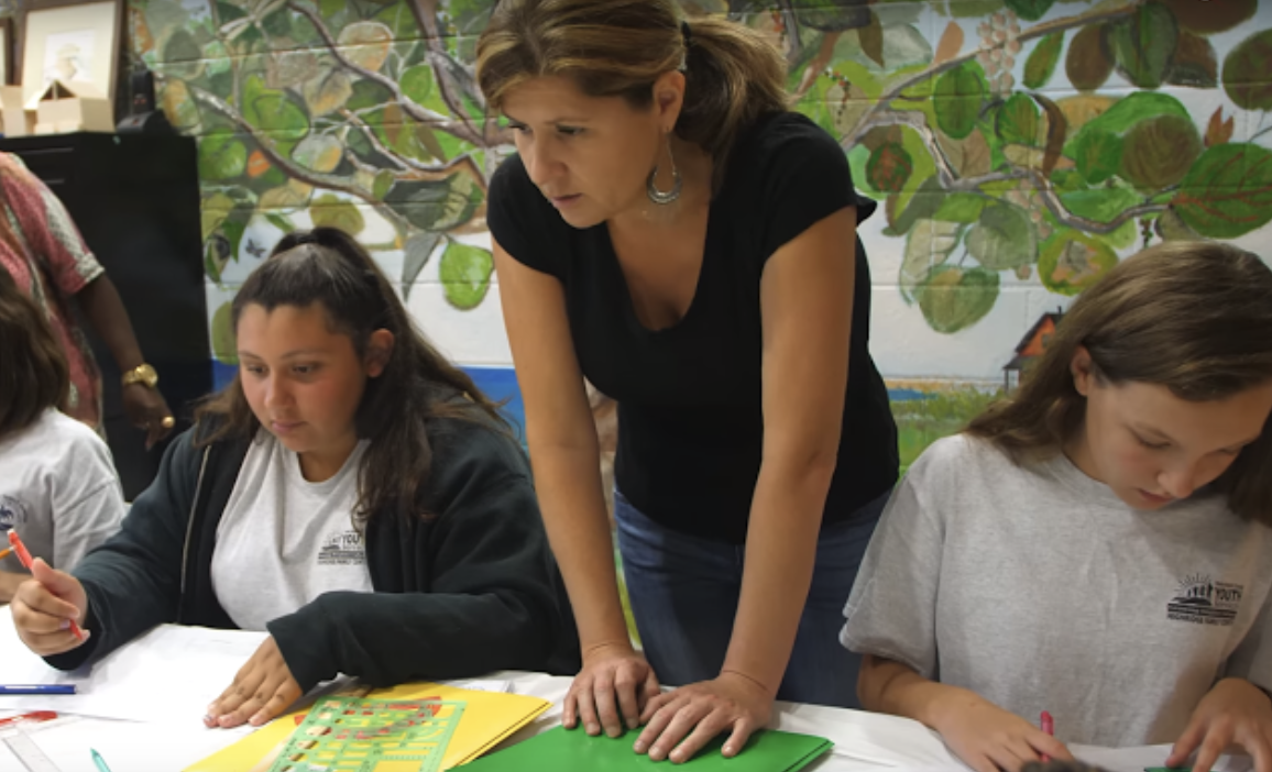 At the Norton Museum of Art's After-school Outreach Program, Erika Cespedes assists her students as they learn to draw shapes with stencils.  Ms. Cespedes had worked at the museum since 201
