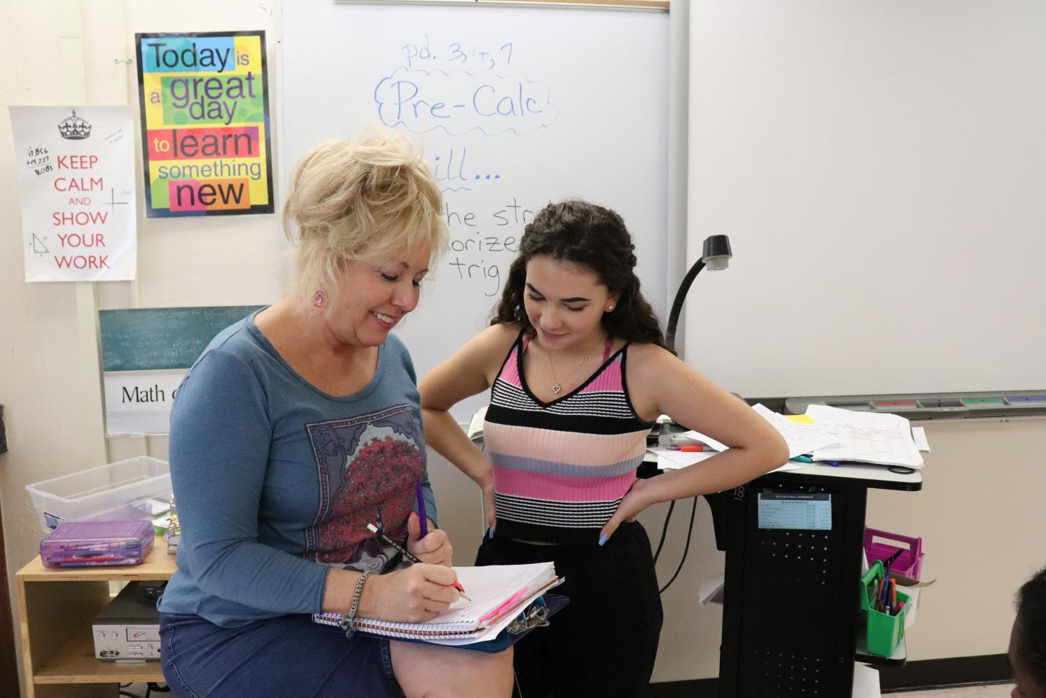 Math teacher Lisa Holland demonstrates Algebra 2 concepts to communications junior Sydney Greenspan. Holland believed that her experience as a teacher helped her tutor kids, as she got to see the learning styles of many different students.