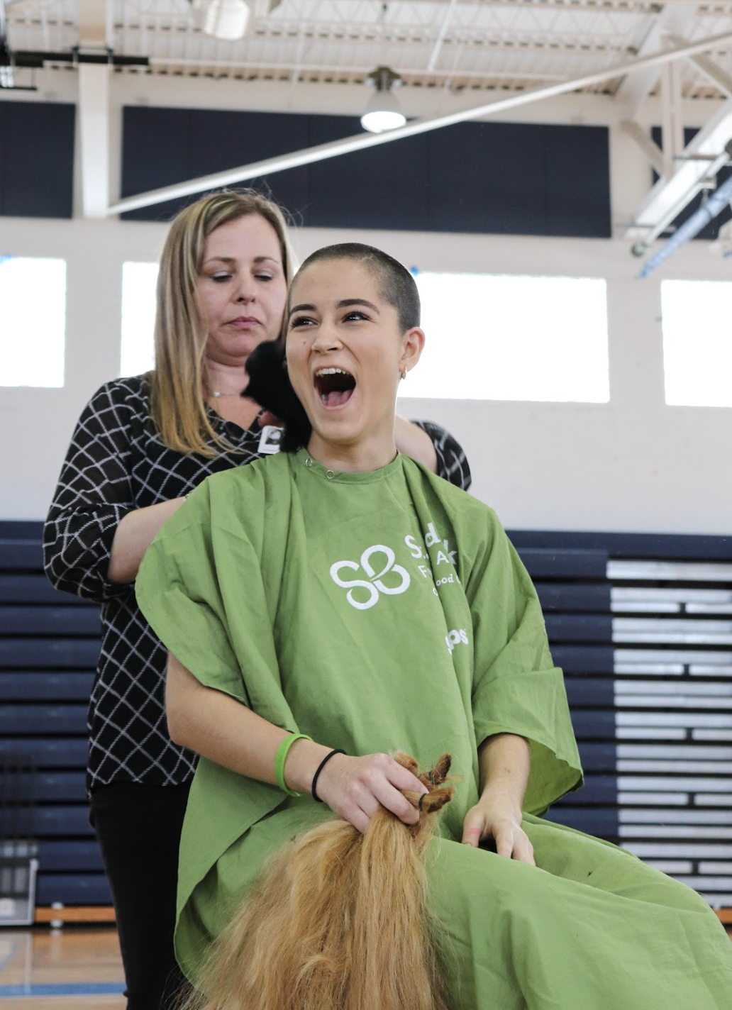 "Communications sophomore Milani Gosman shaves her head in support of the St. Baldrick's Foundation. ""I know that [through St. Baldrick's], I'm not only donating my hair but I'm donating money,"" Gosman said. ""It's such a good environment, they're so nice and the company was so easy to work with it was a great experience."" Gosman was one of 10 students who shaved their heads at the event."