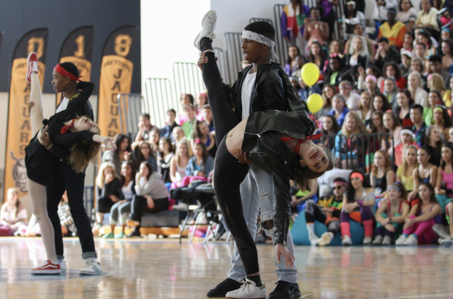 """As dance freshman Morgan Jourdin kicks her leg into the air, dance freshman Alex Thomas looks to his fellow freshmen for support as the audience cheered them on. The freshmen's primarily """"Grease"""" inspired dance reflected the 50s and came in third place overall."""