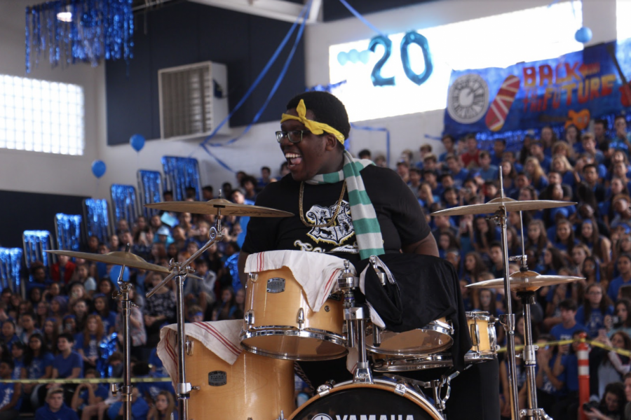 Strings senior Allen Cadet plays drums during the pep rally karaoke competition.