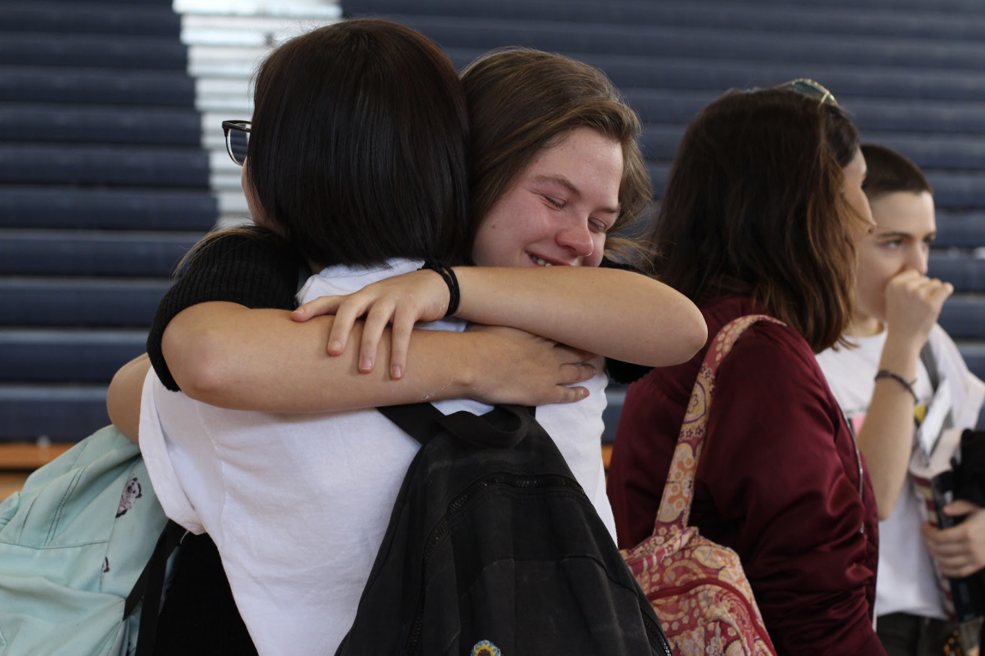 "Digital media sophomore Dani Walters embraces a fellow student following the memorial ceremony for the victims of the Marjory Stoneman Douglas High School shooting in the gym during lunch. ""There are a lot of people who are very sad about this, and we need to unite, and that's what [the memorial] is for,"" dance senior Lauren Clair said. Many students stayed behind in the gym after the performances and presentations to sign a poster that will be given to the students of Stoneman Douglas, learn about donating their prom dresses to students affected by the massacre, and to gather refreshments."