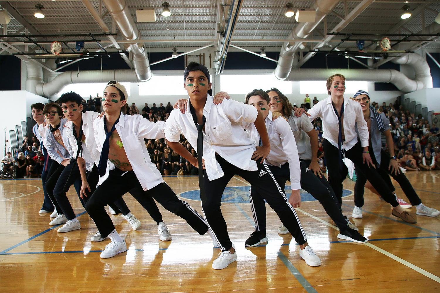 """Visual sophomore Sergio Aries guides his fellow """"cheerleaders"""" into the next dance move, as the crowd cheers them on. The sophomores placed third overall in the powderpuff cheerleading competition."""