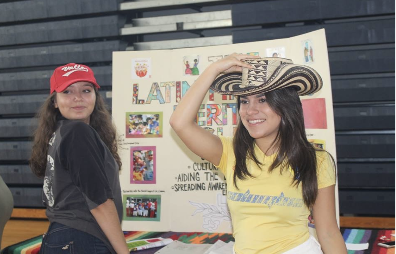 "Communications junior and Latin Hispanic Heritage Club President Catalina Correa stands with vocal junior Diana Parra at their table during the 2017 Club Rush. The aim of the club is to provide space for those with Hispanic or Latin heritage to meet and share their experiences. ""It allows people to see that Dreyfoos actually is a diverse place,"" Correa said. ""It also lets Latino students know that they're not alone."""