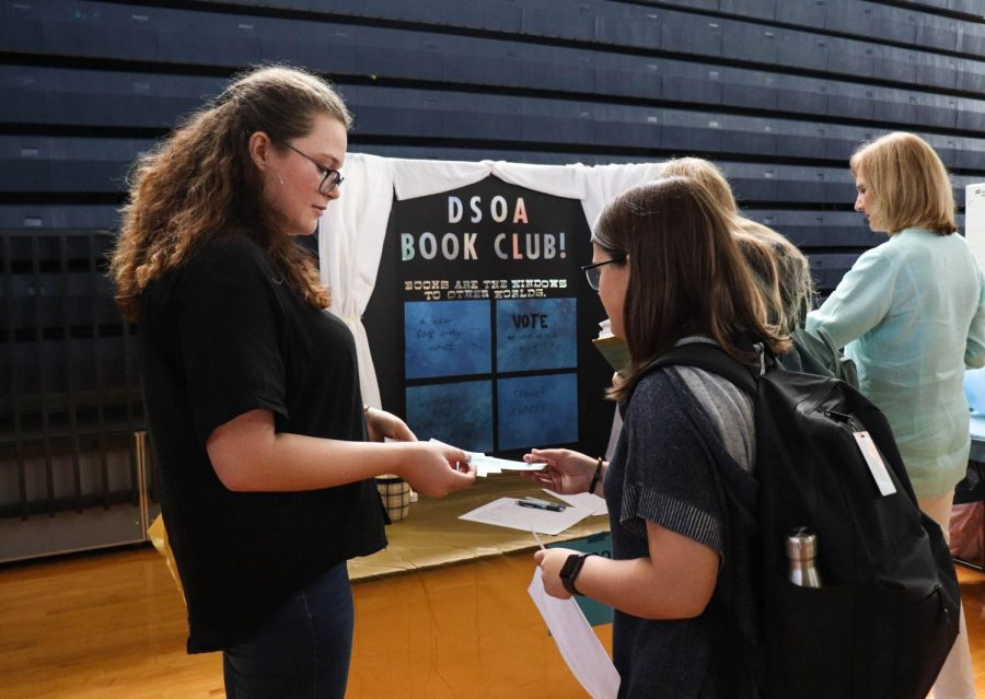 "Book Club founder and communications junior Cassie Glover distributes hand-painted bookmarks to interested students. ""Books are just an amazing way to escape when things get rough,"" Glover said. She hopes that her club can be a stress reliever for students."