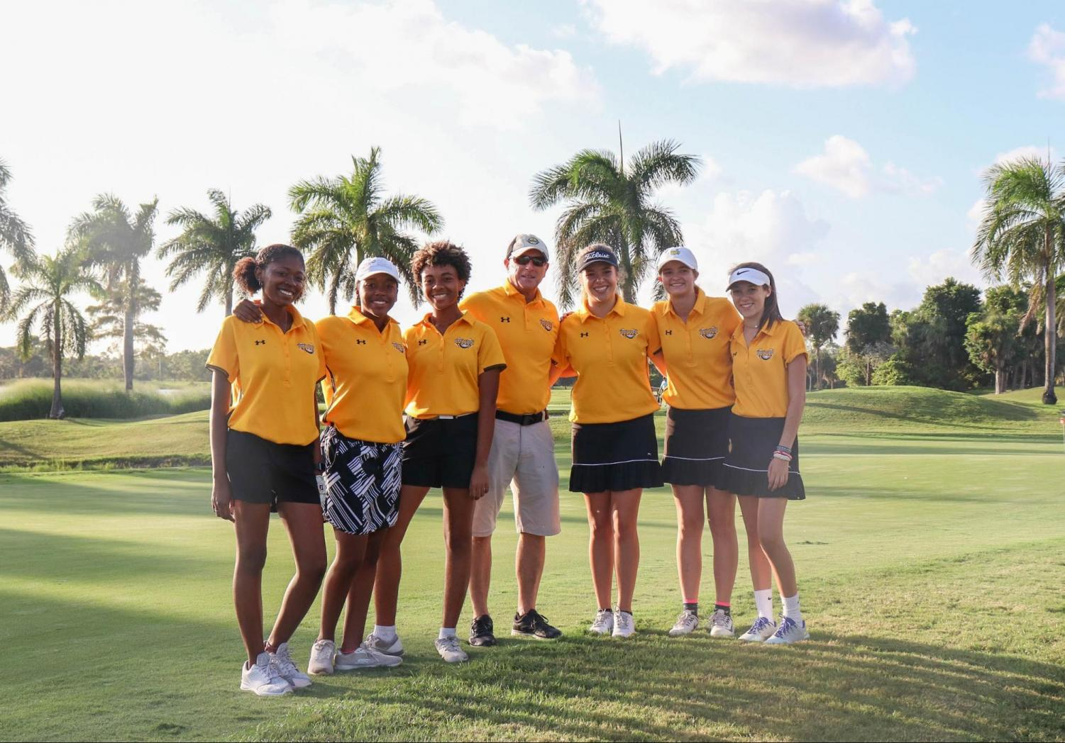The girls' golf team stands unified in black and yellow having finished their match on Oct. 3 at Okeeheelee Park. Matches like this are helping the girls prepare for FHSAA District Girls' Golf Tournament at the end of the season. (L-R) Visual junior Myah Clemons, piano freshman Janise Tucker, visual sophomore Kailyn Bryant, girls' golf coach and School Counselor Mark Carson, communications senior Lilly Randolph, theatre sophomore Emma Troast, and communications freshman Marion Randolph hope for the best at the upcoming matches.
