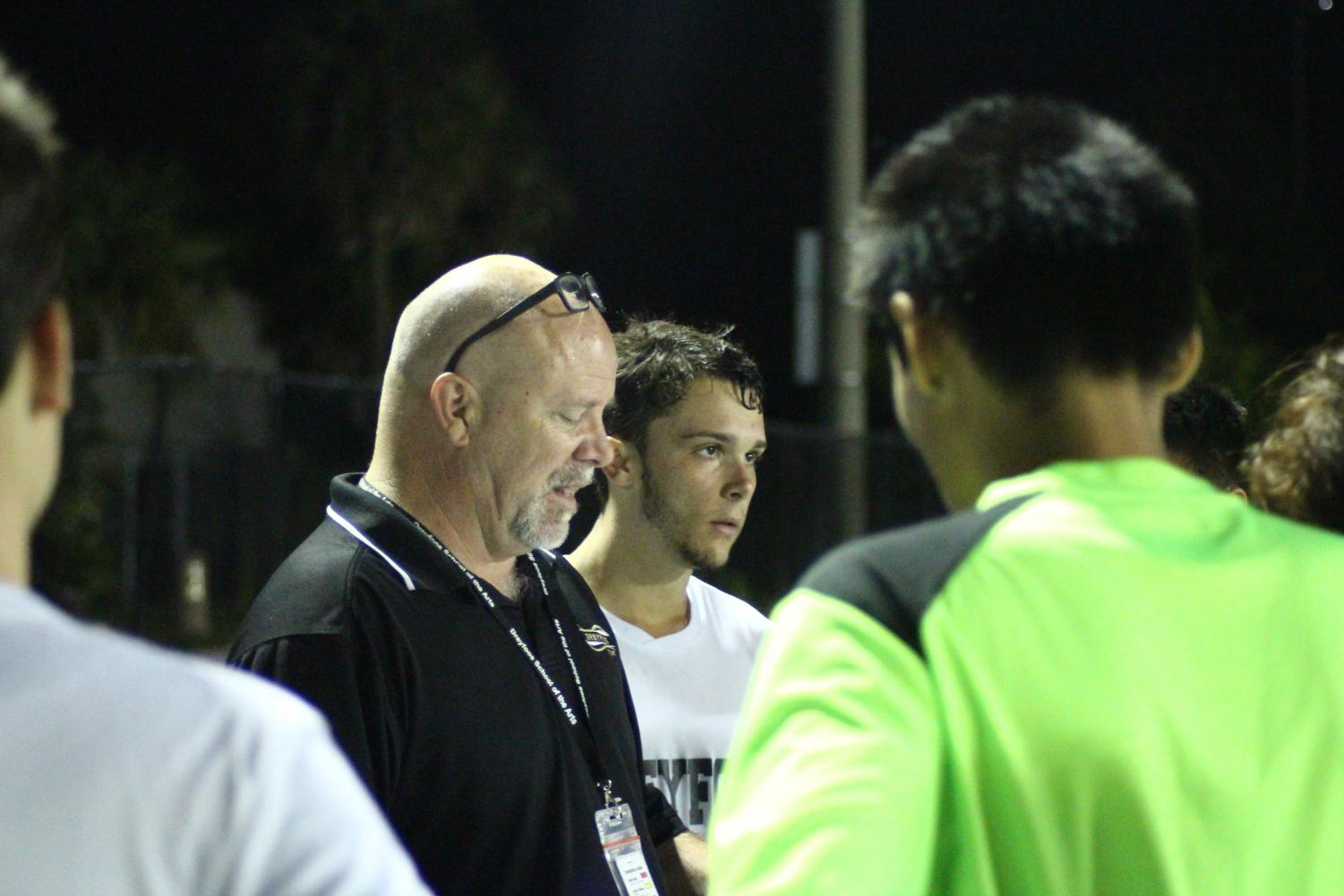 "Co-captain and communications senior Louis Dirienzo stands beside foreign language teacher and Dreyfoos boys' soccer coach Thomas Ruth as he instructs the team for the second half of the game. After losing 3-1 to Palm Beach Lakes High School on Nov. 12 in their first game of the season, he still maintains hope for the long season ahead. ""I am very proud of my guys' effort. [It was] a great game and goal,"" Mr. Ruth said. ""I really didn't know what to expect, and I saw that we have a lot of talent and it will get better."""