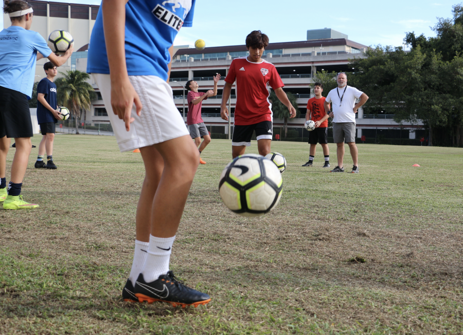 Theatre sophomore Xavier Zambrano pops the ball into the air with a swift kick as foreign language teacher and boys' soccer coach Thomas Ruth watches the player's technique.With both a new coach and new players, the boys' soccer team has been preparing diligently for the season. Their first game is Monday, Nov. 12, at Palm Beach Lakes High School at 8 p.m.