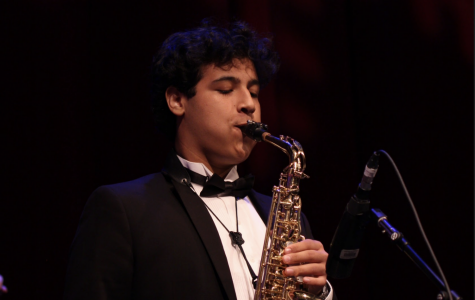 "Band junior David Galli plays the saxophone alongside other performers at Prism. Behind the curtain, stage crew members moved instruments and equipment into place for the next performance. Piano junior Jacques Coury was among the stage crew members working behind the scenes. ""There's really not a dull moment [at Prism],"" Coury said. ""We're always doing something, and there's always something we can be doing to make [the performance] run smoother."""