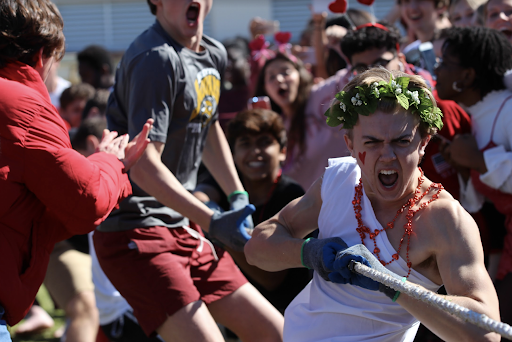 Dressed in a toga with a red heart drawn on his cheek for the Valentine's Day theme, communications junior Tommy McCabe shouts while pulling the tug-of-war rope. Cheered on by classmates on the sidelines, the junior class won.