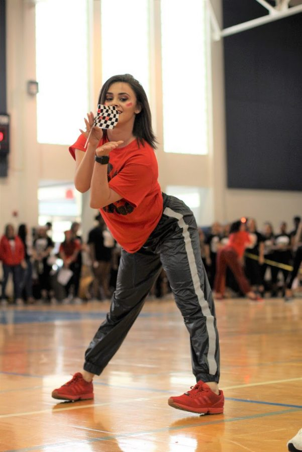 For the second time in the Pep Rally, dance junior Alexa Olivier prepares to toss a checkered flag across the gym floor. Following a music mishap during their first performance, the juniors repeated their dance before winning the event.