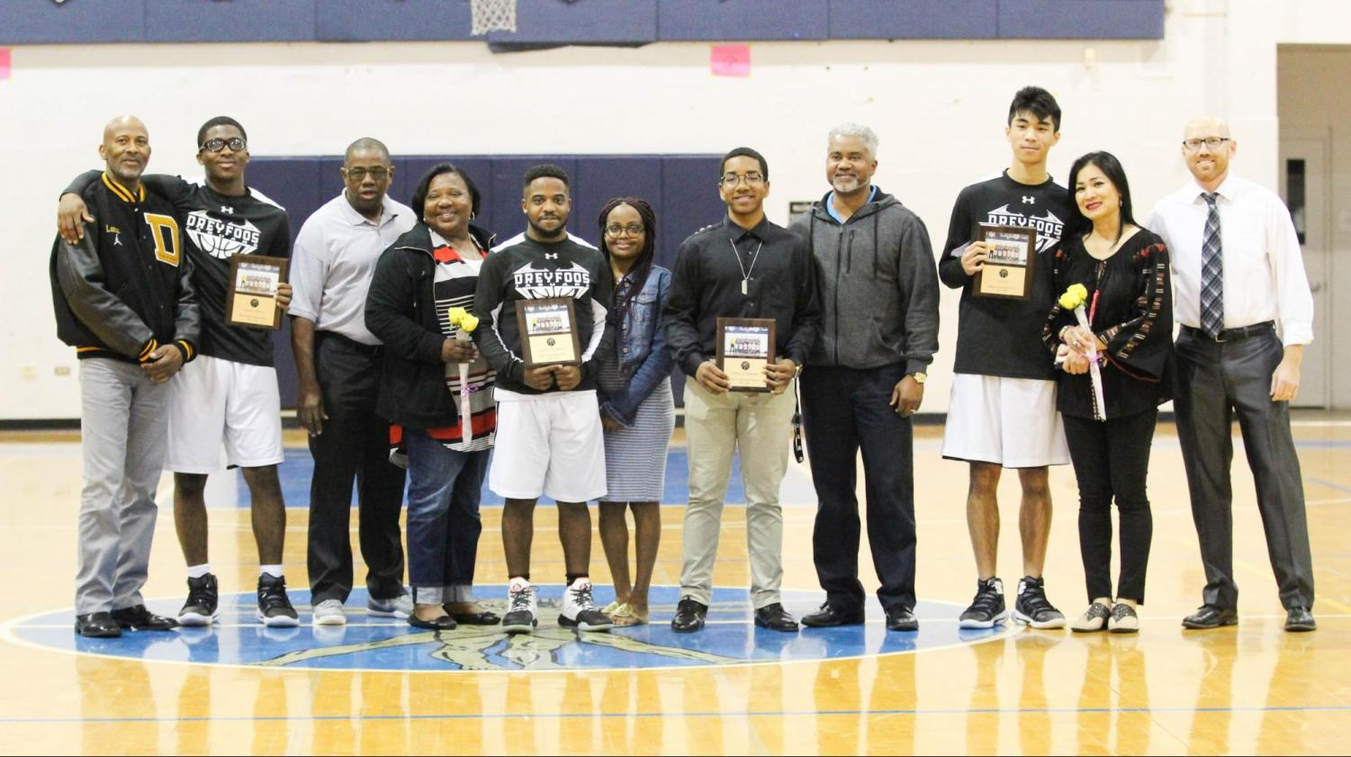 "(Players from left to right: visual senior Lance Carter, vocal senior Jaylen Thompson, visual senior Nickolas Pressoir, and strings senior Alan Le) The seniors of the basketball team stand with parents at their last home game of the year on Jan. 24. Basketball coach and math teacher Matthew Vaughan (far right) smiles as he looks back on the growth of the team this season. ""This is my first year coaching [the basketball team], so I had to earn their trust. But after our first win, things started to click with the team,"" Vaughan said. ""Every time we played [a team] for the second time this year, we have come back and done leaps and bounds better."""