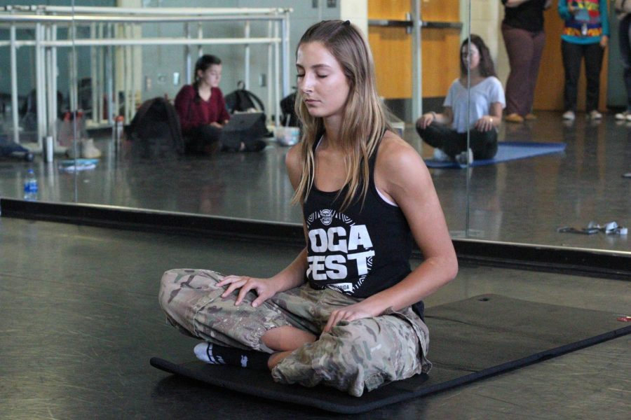 "Visual Senior Paige Duffack sits in Lotus position as she leads several fellow students in meditation. ""I believe mental health is widely underplayed, even though it is what dictates your mental state 24/,"" Duffack said. ""It's important to bring awareness & support to your mental health so you can live your life happier & healthier."" The yoga session Duffack led was Wednesday's activity meant to focus students on de stressing and finding relaxation."