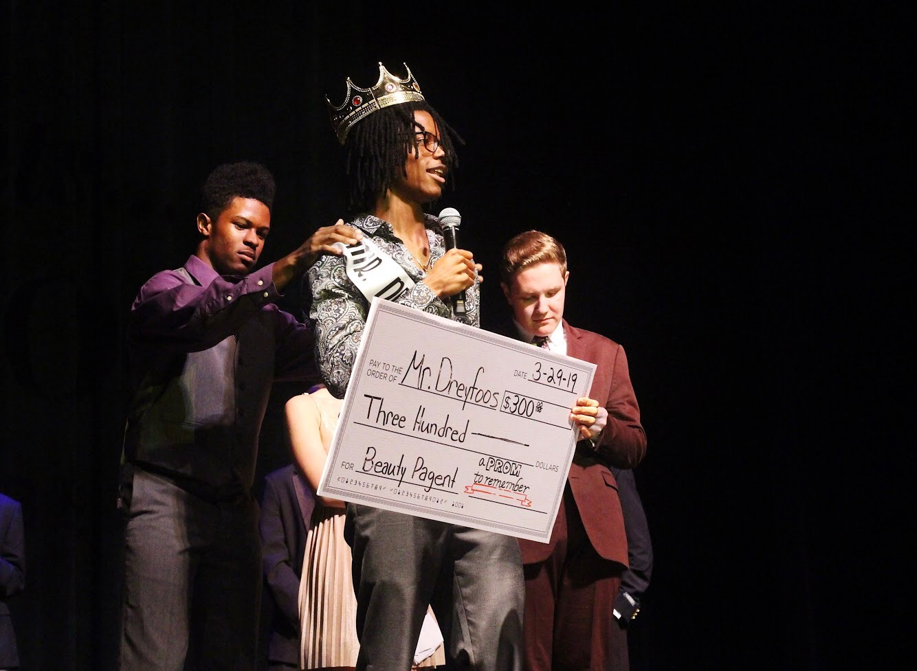 """Visual senior Njari Anderson receives a check for $300 as he gets crowned the next Mr. Dreyfoos. Anderson expressed how he """"can't thank everyone enough"""" as he posed in his crown and sash for the audience."""