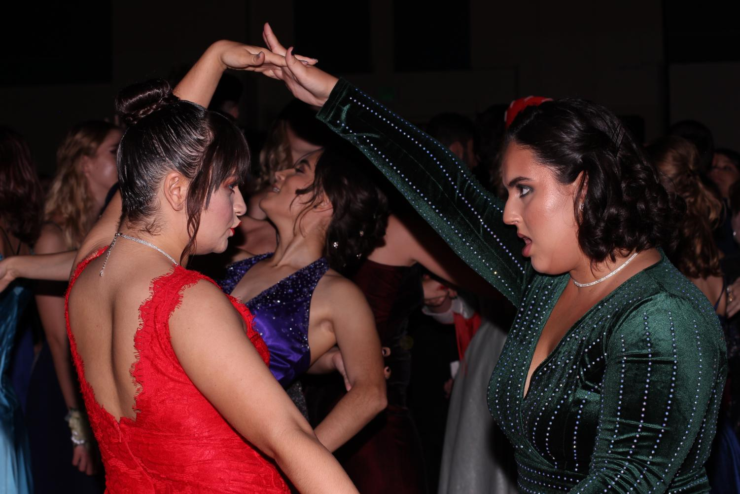 Visual senior Lily Moore and digital media senior Laura Cruz dance, wearing colorful dresses. Prom, thrown for the juniors and seniors, was held at the Palm Beach County Convention Center.