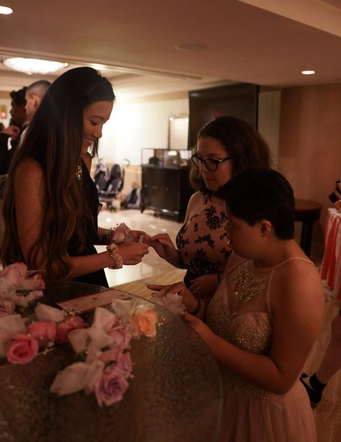 "Two prom attendees carefully pick out a corsage to match their bejeweled gowns before they walked the red carpet. ""I met and talked to so many patients,"" communications junior Sasha Monaco said. ""They inspired me so much with their resilience and their positive attitudes."""
