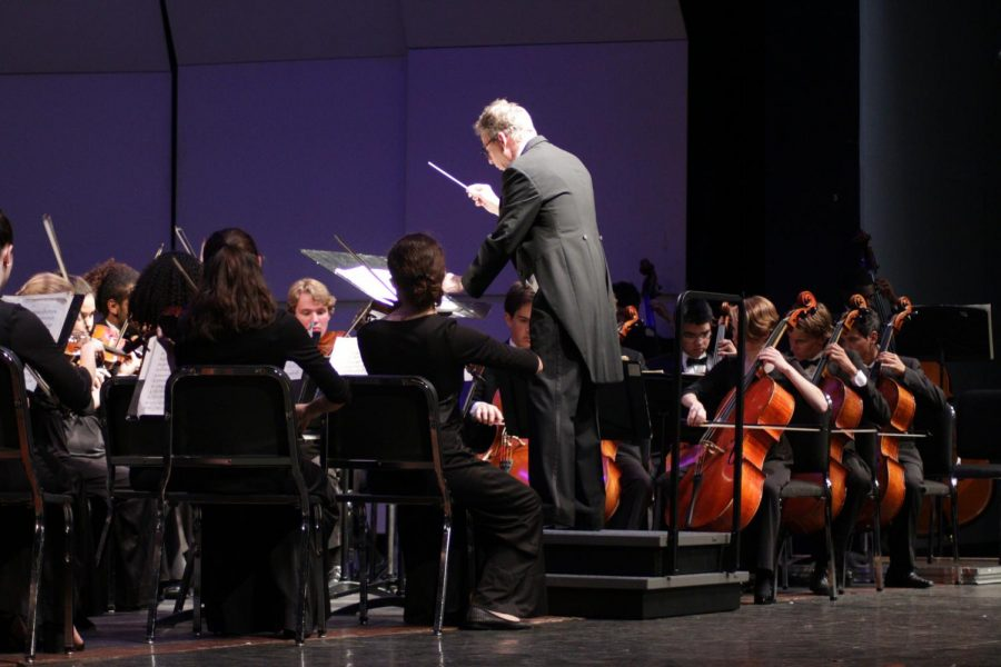 """Mr. Simmons conducts the ensemble, leading them through lengthy pieces and various harmonies. The breaks between the sections of the songs were filled by quiet murmurs from the audience. The final piece, """"Superman,"""" received a standing ovation."""
