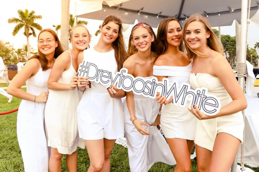 Dance majors pose with a Dreyfoos in White sign before leading guests to their tables, where they enjoyed dinner and drinks before the dancing and raffles started.