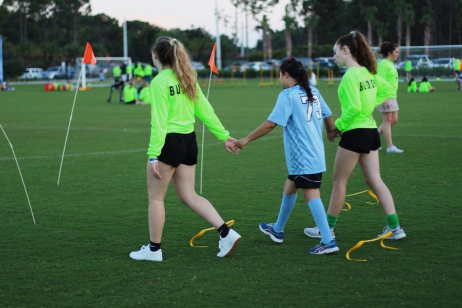 "TOPSoccer volunteers help their buddies participate in a drill before the end of the session scrimmage. ""They all get so happy and excited when kicking the ball,"" communications freshman Cameron Wilson said. ""It's the little things that make their day and mine."""