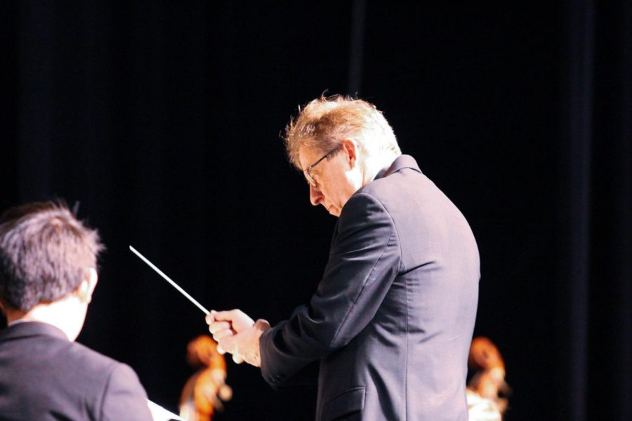 """Strings teacher Wendell Simmons conducts students of all grades at the Strings Orchestra Concert. During a brief intermission between the two pieces, Mr. Simmons addressed the audience. """"The students have] worked hard,"""" Mr. Simmons said. """"This is a short concert, but I think you'll enjoy this."""""""