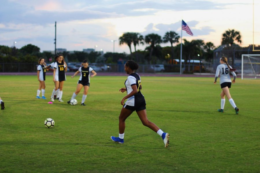 "Band freshman Ava DeGaetano receives the ball from a teammate in preparation for their game. They focused on pass accuracy during the warmup, a strength the soccer team has been working on. ""We connect very well with each other,"" DeGaetano said, ""on and off the soccer field."""