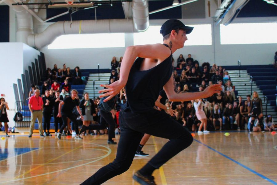 Strings senior Justin Toterella runs to scoop up the dodgeballs sitting in the center of the gym. Dressed completely in black, Toterella fit right in with the rest of his team members, who also wore black for the seniors' goth theme.