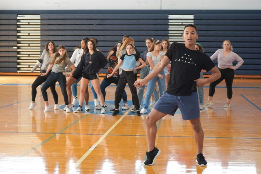 Mason Evans, dance sophomore and choreographer for the sophomore pep rally dance, executes a new move while rehearsing with his dancers.