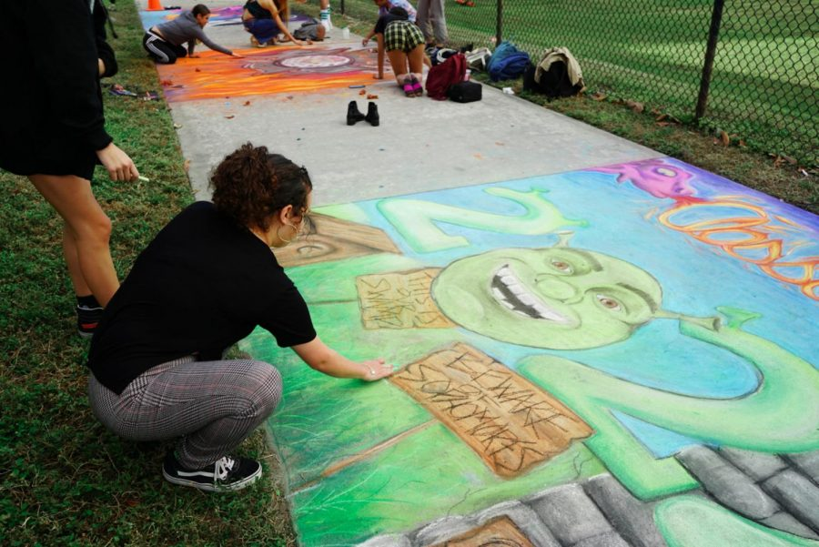 """Visual sophomore Alyssa Gonzalez finishes the """"Shrek"""" 2022 portrait for the Generation Day sidewalk chalk competition. """"Last night, we worked on it for three hours and this morning we added finishing touches,"""" Gonzalez said."""