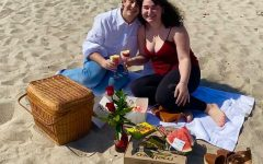 Kayla Esther Zakarin, right, and her boyfriend, left, sit on the beach holding wine glasses filled with cake.