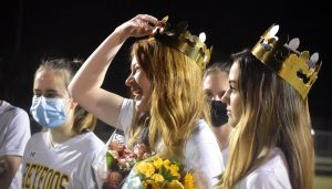 Senior, left midfield, Katelyn Carter smiles as she is given flowers and a crown by her teammates. Players surround her and celebrate senior night while following  COVID-19 guidelines.