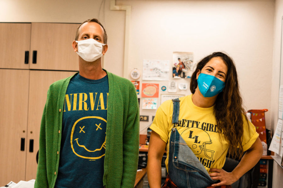 """Nathan Hesse and Carmen Gallardo throw back to 1990's grunge with a Nirvana t-shirt, overalls, and a flannel. The term grunge originated as a descriptor for an emerging style of music popularized by Nirvana, Pearl Jam, and Soundgarden, which grew into a genre of clothing that considered itself """"anti-fashion."""" Photo by Allison Robbert."""