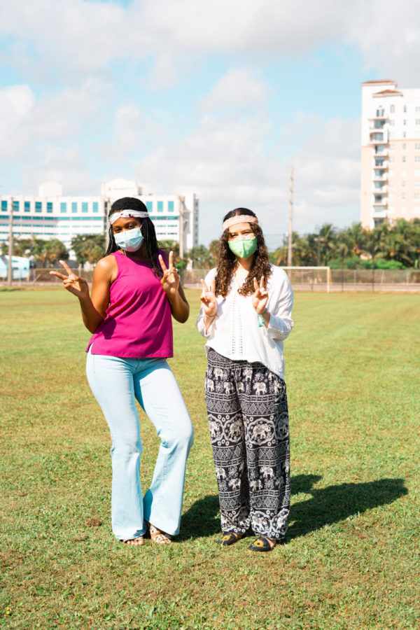 """Teneisha Finney and Sarah Garcia display peace signs in true hippie spirit. The symbol was originally used as a """"V"""" sign for victory by the Allied Nations in World War II, but was reclaimed by anti-war activists in the 1960s. Photo by Allison Robbert."""