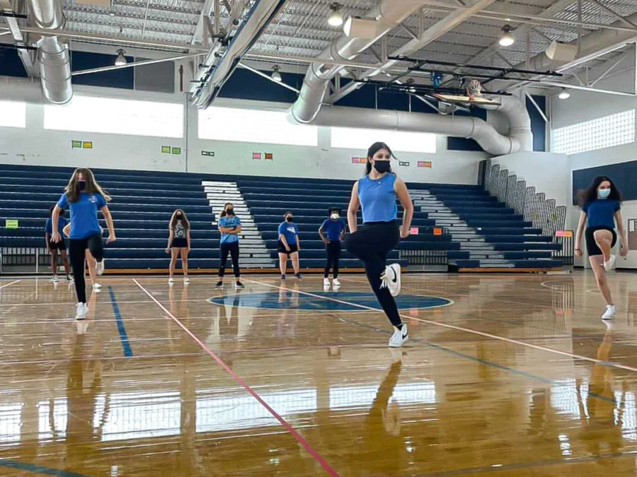 Dance freshmen Savannah Ehrlich, Isabella Passos, and Anna-Sofia Machado stand centered on the gym floor, practicing their routine before the final take for the freshman pep rally dance.