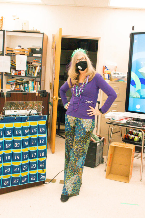 English teacher Martha Warwick poses in a Mardi Gras ensemble, pairing vibrant pants with a layer of purple, gold, and green beads. These colors are traditionally associated with the holiday and have been assigned to symbolize justice, power, and faith respectively. Photo by Allison Robbert.