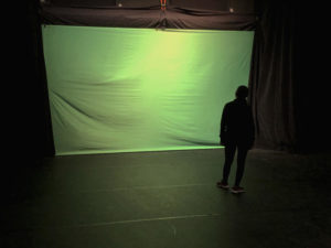Theatre junior Sunaina Singh removes wrinkles from a green screen. Recording the show has allowed for changes in scenic design.
