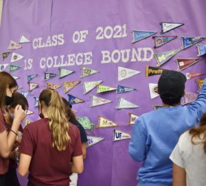 Students gather to hang pennants on the cafeteria wall. Seniors were asked to decorate their pennants with their college logos prior, though decorating materials were available at the event.