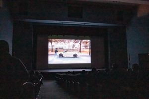 """On screen, theatre junior Ryan Lamontagne walks to his car as part of the film he starred in, """"When I Look in Your Eyes."""""""